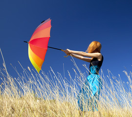 Redhead girl with umbrella at windy grass meadow.