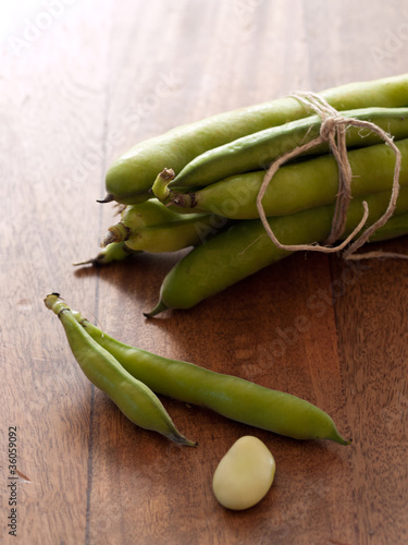 green beans on wooden board tied with kitchen string
