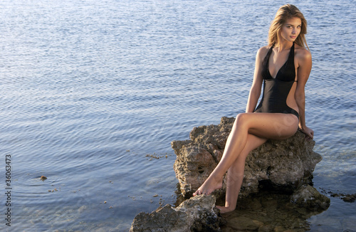 Beauty on a beach sitting on rock