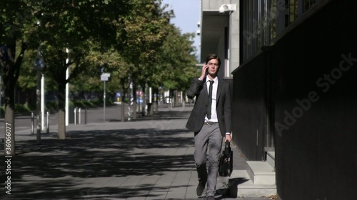 Young man speaking with telephone and walking in the city