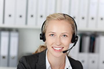 lächelnde blonde geschäftsfrau mit headset