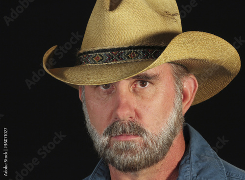 A Man with a Gray Beard in a Straw Cowboy Hat
