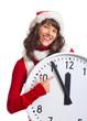 lachende Weihnachtsfrau zeigt auf Uhr