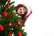 lachende Frau schaut hinter Weihnachtsbaum hervor