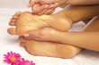 Fussmassage einer jungen Frau durch Therapeutin