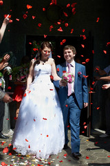 Happy newlyweds and flying red petals