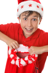 Excited boy holding a red Christmas sack