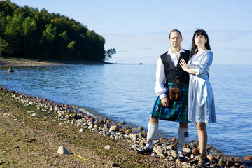 Woman and man in scottish costume near the sea.