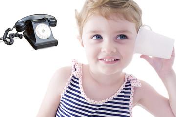 Bambina con telefono senza fili e telefono nero