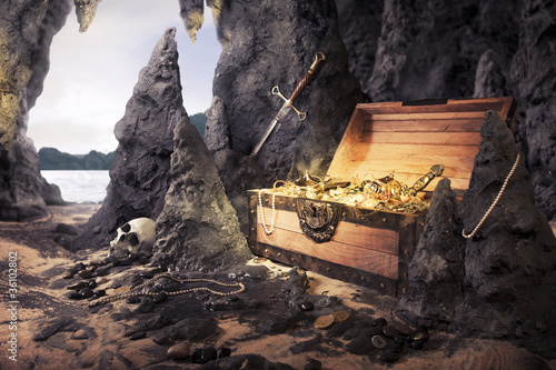Leinwanddruck Bild open treasure chest with bright gold in a cave