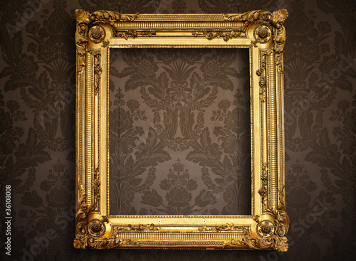 Empty golden painting frame on vintage wallpaper
