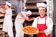 Male baker holding a pizza in bakery