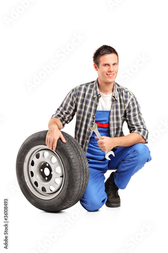 A male mechanic posing with a spare tire and holding a wrench