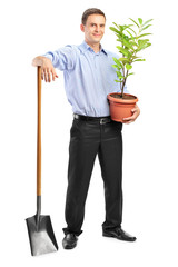 Smiling man holding a plant and a shovel