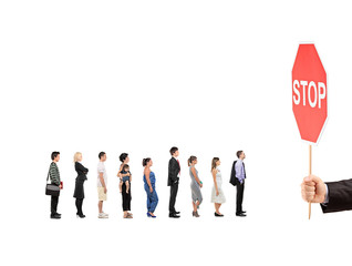 People waiting in line and a hand holding a stop traffic sign