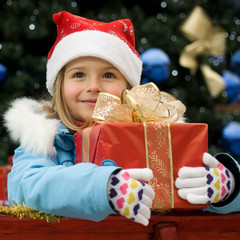 Christmas - portrait of cute girl with Christmas gift in sledge