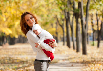 Young mother with sleeping child on hands in autumn park