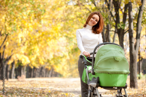 Happy young mother with baby in buggy