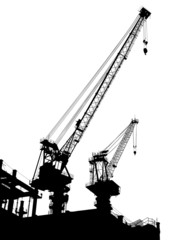 Silhouettes of two cranes on building
