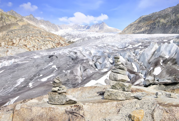 Stacked rocks with blue sky and Rhone glacier as background