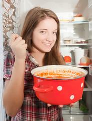 girl eating  soup from pan near fridg