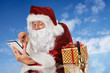 Santa Claus with tablet pc, gift and bell