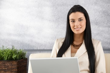 Young businesswoman working on laptop smiling