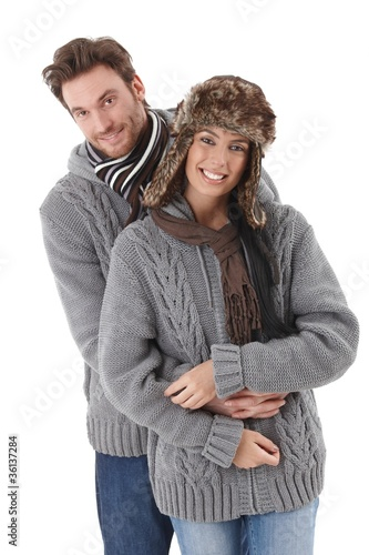 Young couple wearing the same sweater smiling