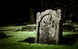 Gravestone with skull and bones in old cemetery, dramatic light - 36142215