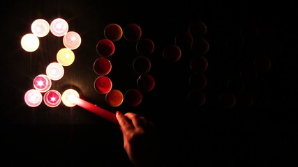 2012 made ​​of colored candles on a black background