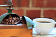 Antigue coffee grinder with beans and cup