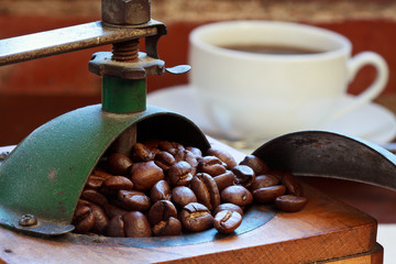 Macro of antique coffee grinder and coffee cup