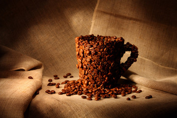 Image of mug covered with coffee beans on canvas background