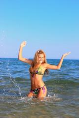 Sexy bikini model having fun in the ocean