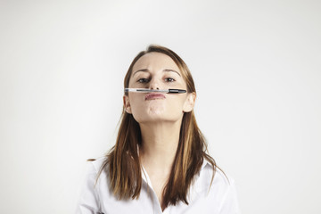 young businesswoman holding pen with his nose