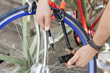 Close-up of a man's hands locking his bicycle, Paris, Ile-de-France, France