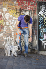 Man showing feces to his puppy, Paris, Ile-de-France, France
