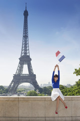 Woman holding a French flag sitting on a stone wall with the Eiffel Tower in the background, Paris, Ile-de-France, France