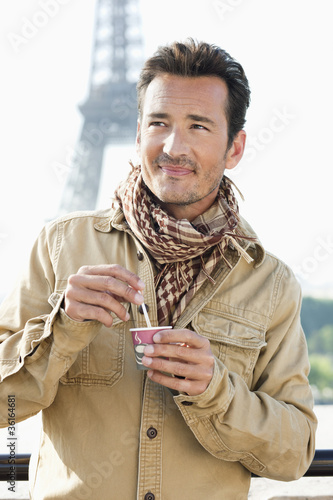 Man holding a disposable cup with the Eiffel Tower in the background, Paris, Ile-de-France, France