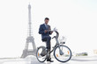 Businessman holding a newspaper and a mobile on a bicycle with the Eiffel Tower in the background, Paris, Ile-de-France, France