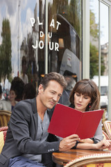 Couple reading menu at a restaurant, Paris, Ile-de-France, France