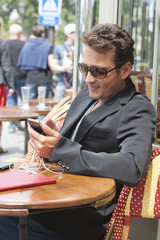 Man using a mobile phone in a restaurant, Paris, Ile-de-France, France