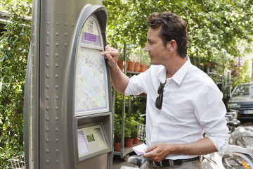 Man looking a map in a ticket machine, Paris, Ile-de-France, France
