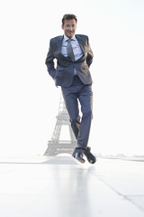 Businessman jumping with the Eiffel Tower in the background, Paris, Ile-de-France, France