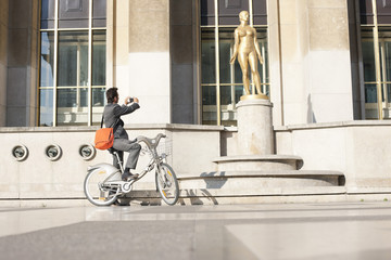 Man on a bicycle taking a picture of a woman's statue, Palais de Chaillot, Paris, Ile-de-France, France