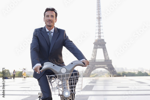 Businessman riding a bicycle with the Eiffel Tower in the background, Paris, Ile-de-France, France