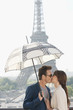 Couple kissing under an umbrella with the Eiffel Tower in the background, Paris, Ile-de-France, France