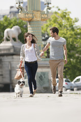 Couple running with a puppy, Paris, Ile-de-France, France