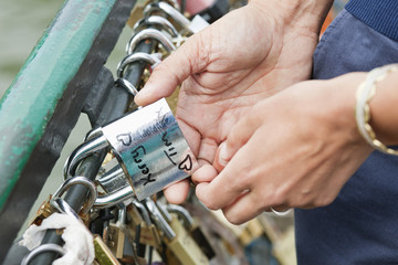 Couple locking a padlock of love on a bridge, Pont des Arts, Paris, Ile-de-France, France