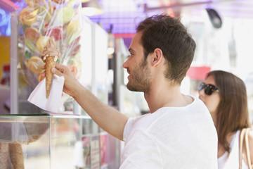 Man taking ice cream from an ice cream parlor, Paris, Ile-de-France, France